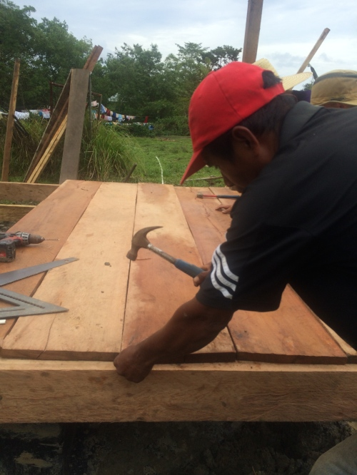 Francisco's family came through with the wood! Here is Simon attaching the floorboards