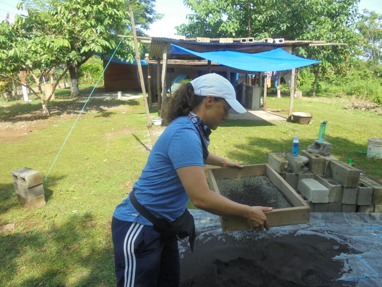 Jen sifting sand that we use in our concrete mixture for the water filters and fuel efficient stoves